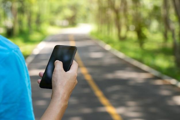 Mens die smartphone op een weg in het park gebruikt