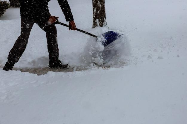 Mens die sneeuw van de stoep voor zijn huis schept na een zware sneeuwval
