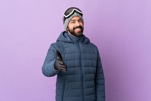 Mens die snowboard over geïsoleerde muur doet