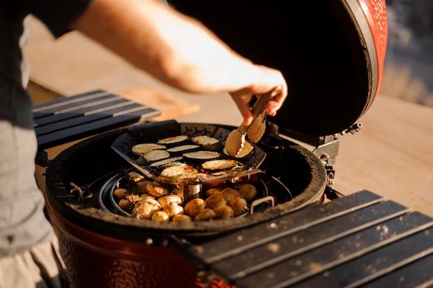 Mens die spaanse pepers, paddestoelen en aubergines op de grill kookt