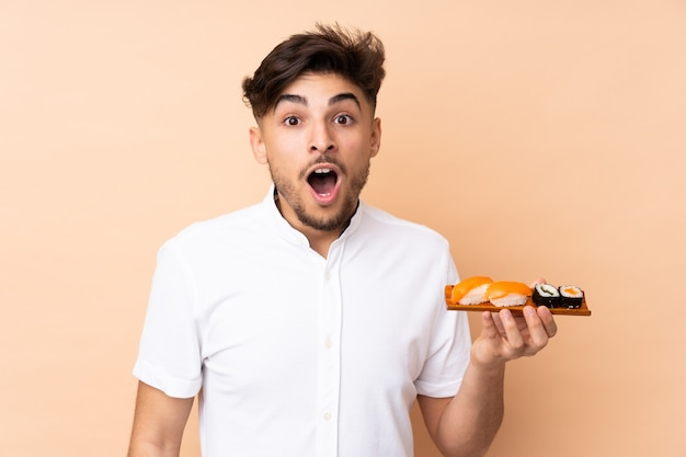 Mens die sushi eet die op beige muur met verrassing en geschokte gelaatsuitdrukking wordt geïsoleerd