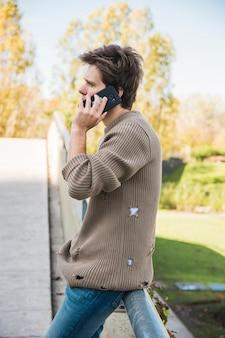 Mens die sweatshirt draagt die op celtelefoon spreekt