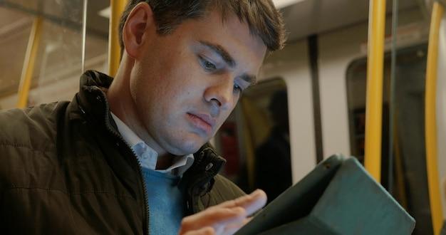 Mens die tablet in de metro gebruiken