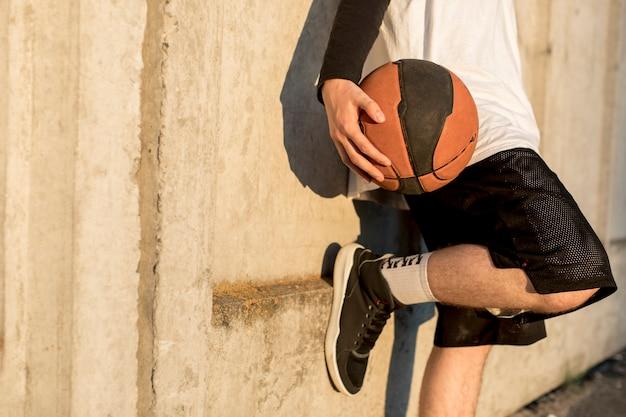 Mens die tegen een muur met basketbal leunt