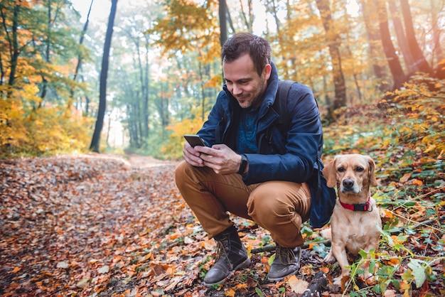 Mens die telefoon in kleurrijk de herfstbos met behulp van