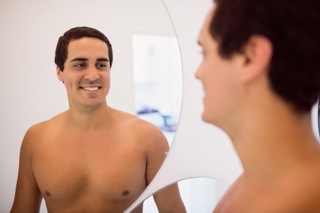 Mens die terwijl status voor de spiegel glimlacht