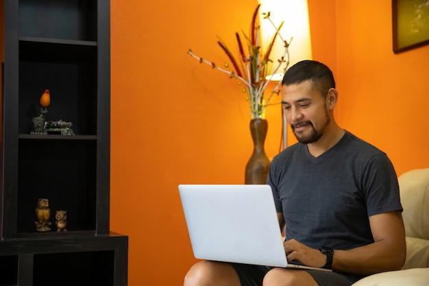 Mens die thuis gebruikend laptop in de woonkamer, huisbureau werken
