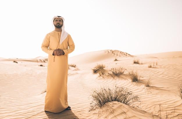 Mens die traditionele vae-kleren draagt die tijd in de woestijn doorbrengen