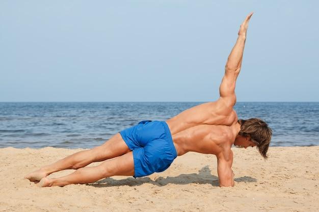 Mens die training op het strand doet
