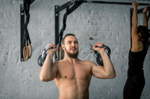 Mens die twee kettlebell trainingoefening opheffen bij gymnastiek