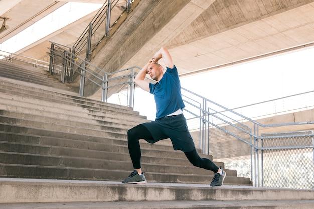 Mens die uitrekkende oefeningen op concrete trappen uitvoert