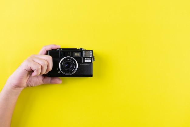 Mens die uitstekende camera op gele achtergrond met exemplaarruimte houdt. wereld fotografie dag concept.
