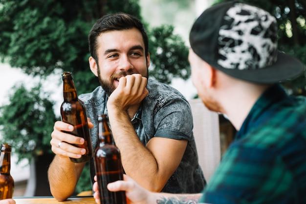 Mens die van bier met zijn vrienden geniet