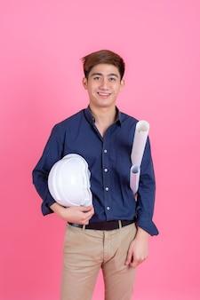 Mens die van de portret de jonge architect witte helm dragen en blauwdruk in hand houden, hij die zich met glimlach bevinden en camera op roze kijken