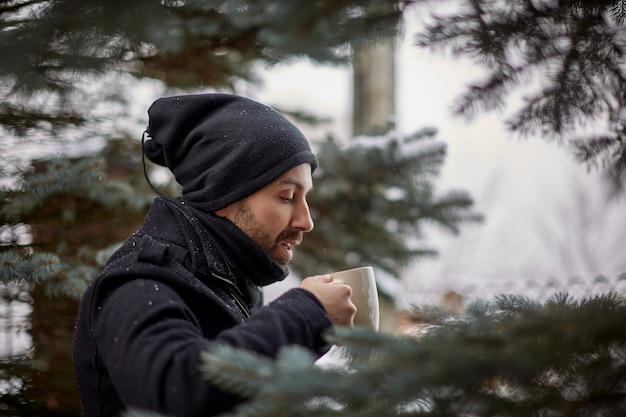 Mens die van hete koffie op sneeuwterras geniet