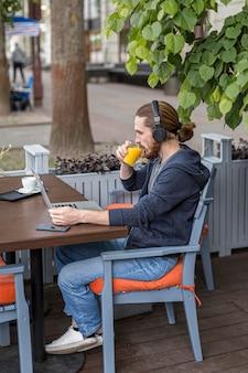 Mens die van sap genieten bij een stadsterras terwijl het werken aan laptop