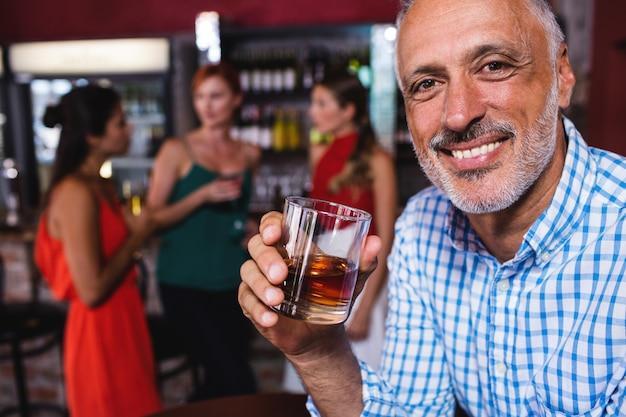 Mens die van whisky in nachtclub geniet