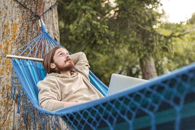 Mens die van zijn tijd in aard geniet terwijl het zitten in hangmat