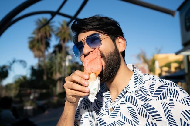 Mens die van zonnig weer geniet terwijl het eten van een roomijs