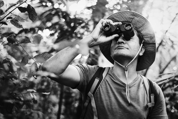Mens die verrekijkers in het bos met behulp van