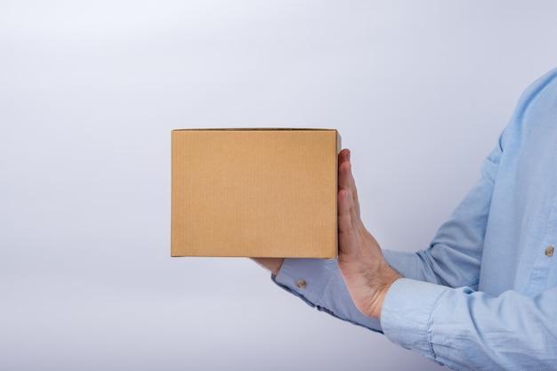 Mens die vierkante kartondoos op witte muur houdt. kopieer ruimte. moke up