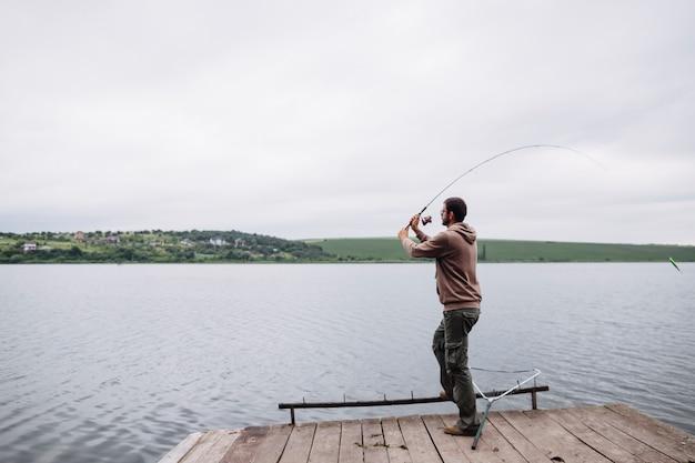 Mens die vislijn in het meer werpt