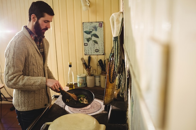 Mens die voedsel in keuken voorbereidt