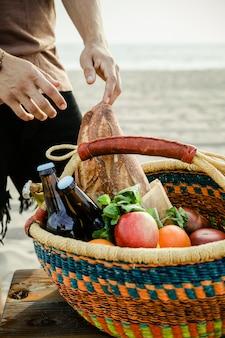 Mens die voedsel van een picknickmand krijgt