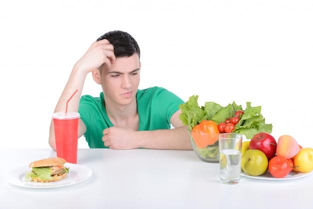 Mens die vooraan een kom salade en een grote hamburger houdt.