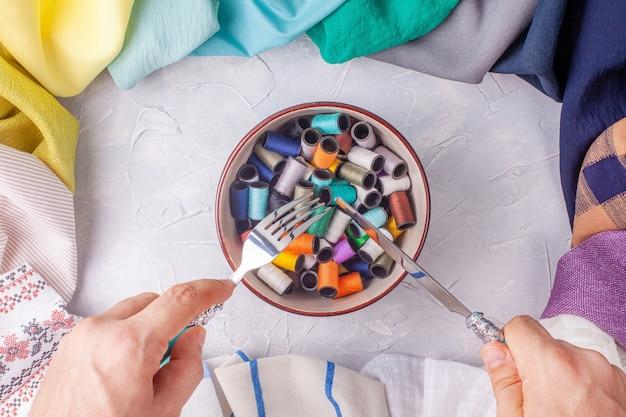 Mens die vork en mes overhandigt onder de kom met spoelen van draad in stoffen veelkleurig frame