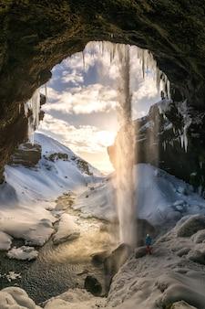 Mens die waterval in sneeuwhol waarnemen bij zonsondergang