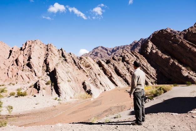 Mens die weg de bergen bekijkt
