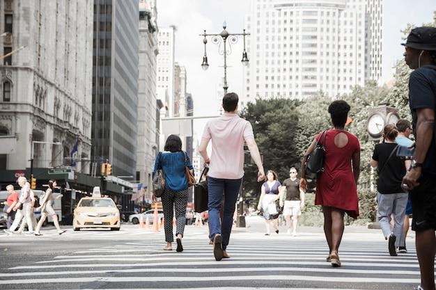 Mens die weg op bezige straat kruist