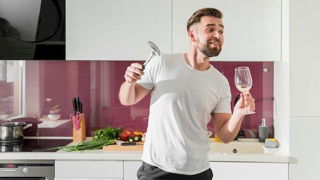 Mens die wijn drinkt en rond in de keuken voor de gek houdt