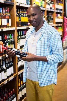Mens die wijnfles bekijken in kruidenierswinkelsectie bij supermarkt