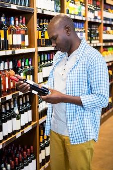 Mens die wijnfles bekijken in kruidenierswinkelsectie