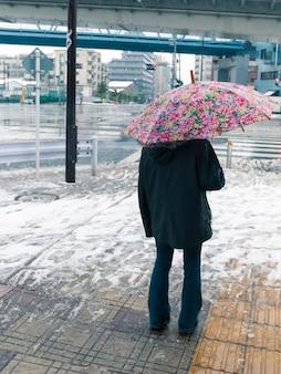 Mens die zich bij de natte gladde stoep onder paraplu tegen de winter in tokyo bevindt; focus op paraplu