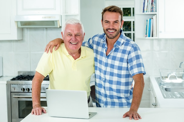 Mens die zich met vader door laptop bij lijst in keuken bevindt