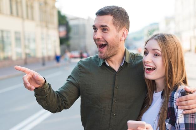 Mens die zich met zijn meisje bevindt dat op iets op straat richt
