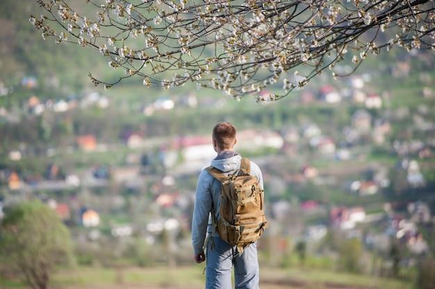 Mens die zich onder een tot bloei komende boom bevindt en bovenop heuvel geniet van