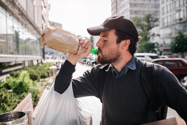 Mens die zich op de straat bevindt en van fles drinkt