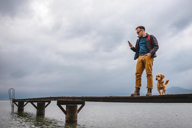 Mens die zich op dok bevindt en slimme telefoon met behulp van