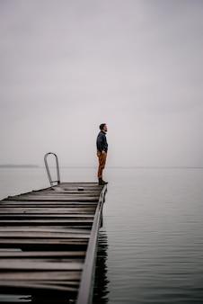 Mens die zich op een oud houten dok bevindt