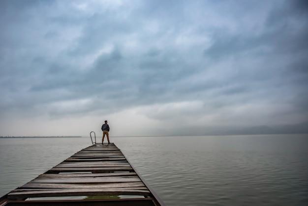 Mens die zich op een oud houten dok in stormachtig weer bevindt