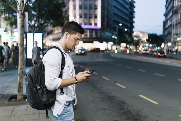 Mens die zich op kant van de weg bevindt die het mobiele telefoonscherm bekijkt