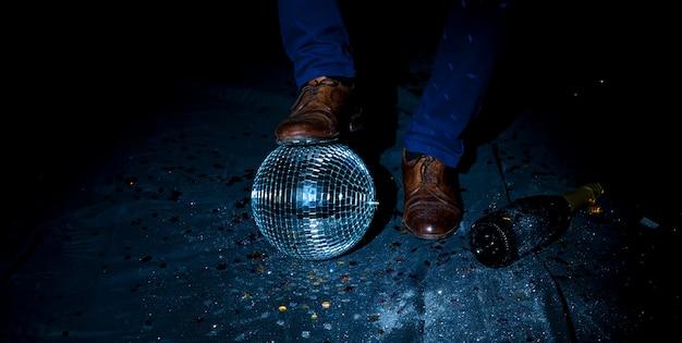 Mens die zich op vloer met discobal bevindt