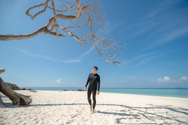 Mens die zich op wit zandstrand bevindt. blauwe zee en lucht landschap. zomervakantie.