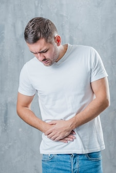Mens die zich tegen grijze achtergrond bevindt die aan buikpijn lijdt