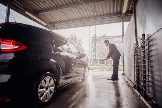 Mens die zijn auto in autowasserette schoonmaken.