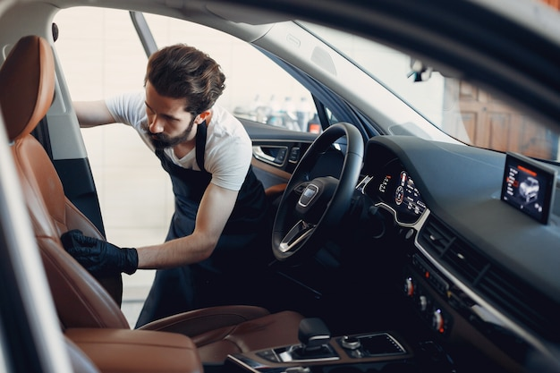 Mens die zijn auto in een garage wast